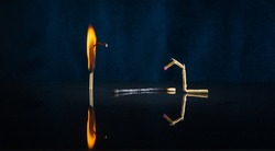 Three matches: one burned, the second is burning, and the third is broken on a dark background with a bokeh effect