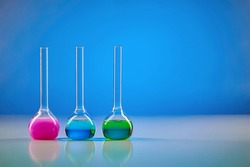 Three medical flasks with colorful chemical reagents for tests, blue background. Laboratory research of Coronavirus. Pandemic COVID-19. Close up