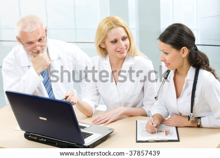 Three medicine workers discuss computer work - stock photo