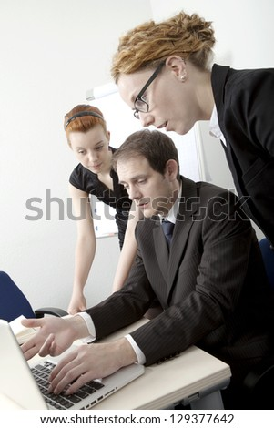 Three members of a business team brainstorming with the man gesturing towards his computer screen which they are all reading