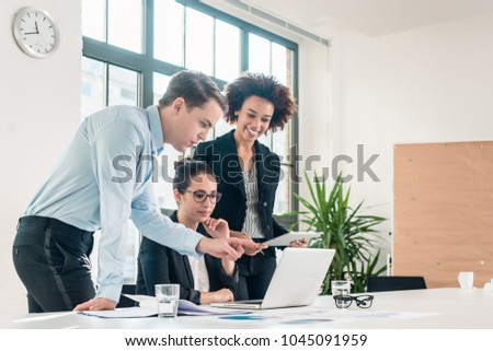 Three members of a young professional team working together in a modern meeting room