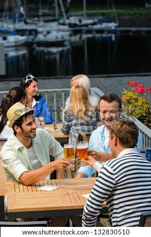Three men drinking beer at terrace bar enjoying night out
