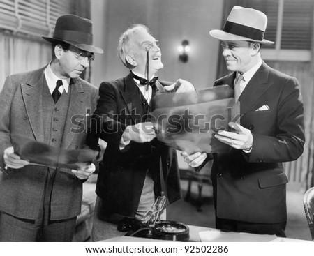three men looking at x rays