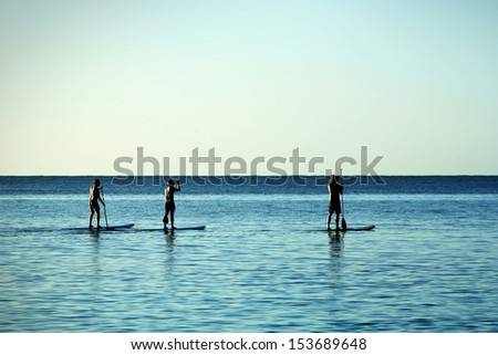 Three men paddle-boarding at Caribbean Sea