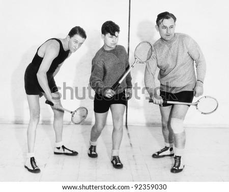 three men playing squash