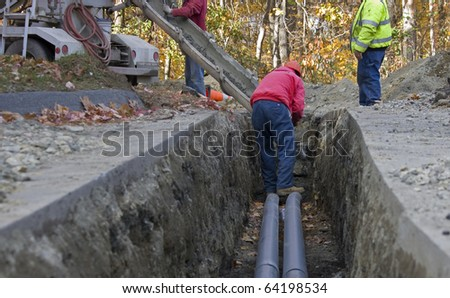 three men pouring concrete in a ditch