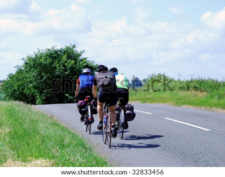 Three men riding bicycles along Yorkshire country road