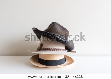 39b5dfd2997dbc Three men's hats stacked on white shelf against neutral wall background  #1321146338