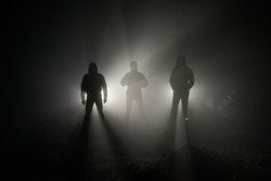 three men's silhouettes in the fog are illuminated by the light of the headlights behind