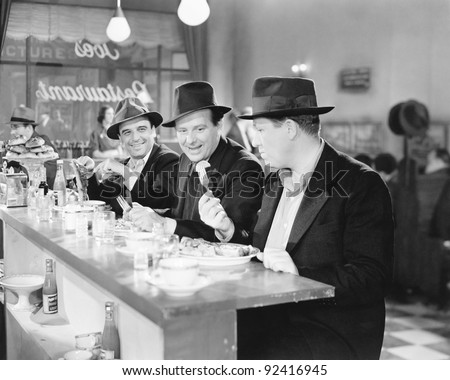 Three men sitting at the counter of a diner
