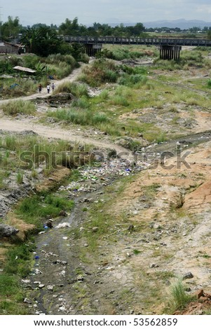 stock photo : three men walk dusty path through polluted river valley in the ...