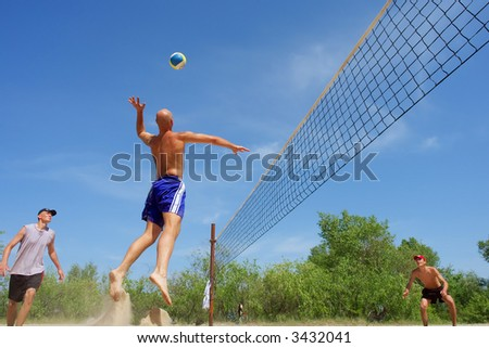 Three men while playing beach volleyball - balding guy prepares to spike the ball. Shot near Dnieper river, Ukraine.