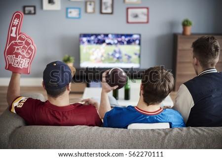 Three men with American football equipment