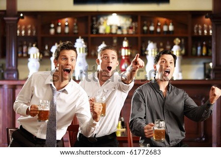 Three men with beer rejoice the victory of their favorite team in the pub
