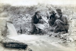 Three men, with dog, panning for gold in a stream in the Black Hills of South Dakota in 1889. Old timers, Spriggs, Lamb and Dillon may be die hard survivors from the Gold Rush of 1876.