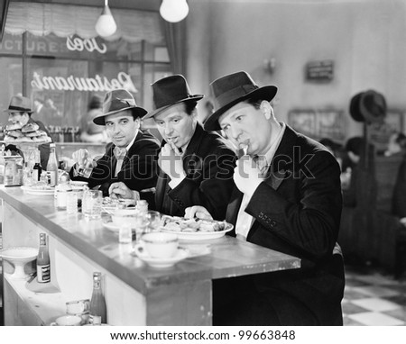 Three men with hats eating at the counter of a diner