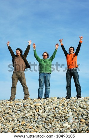 three mens with open arms with the sky as background