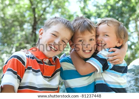 Three merry brothers hugging, in park