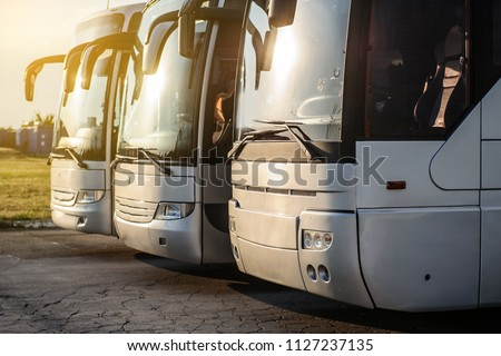 three metallic buses staying in the parking at the sunset