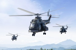 Three military helicopters flying in the blue sky while patrolling in the mountain