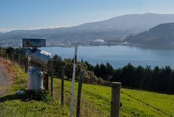 Three milk vats standing on the ground over the ocean in Dunedin peninsula, New Zealand