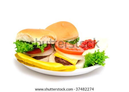 Three mini-burgers topped with cheddar cheese, white onion, tomato and lettuce on a white plate with sliced dill pickles on the side isolate on a white background