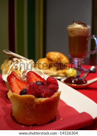 Three mini pies of fruits, with other bakery stuffs and cappuccino.