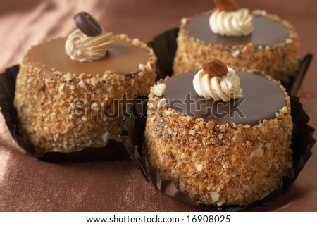 Three miniature chocolate meringue cakes with cream and almonds, shot on golden silk background - stock photo
