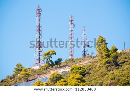 Three mobile antenna towers on the hill - stock photo