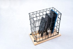 three mobile phones locked in a cage with a padlock, concept of social isolation or phone abuse and social networks, white horizontal background