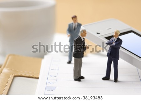 Three models of businessman on the notebook