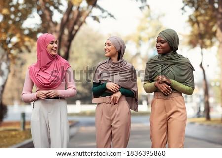 Three Modern Muslim Young Women In Hijab Headscarf Walking In Park Outdoors. Cheerful Islamic Students Ladies Talking Enjoying Walk Outside. Female Frienship, Fashion Concept Stock fotó ©