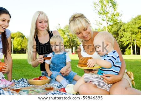 Three mother with kids having picnic