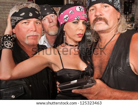 Three motorcycle gang members with beautiful woman in leather