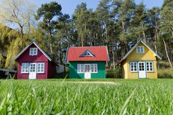 three multi-colored small tiny house on the lawn in the forest