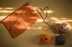 Three multi-colored tangles of yarn, spokes, knitted scarf on a beige background. Bright sunlight and shadow.