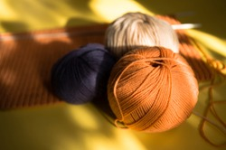 Three multi-colored tangles of yarn, spokes, knitted scarf on a yellow background. Bright sunlight and shadow. Close.