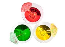 Three multicolored cocktails in martini glasses with umbrellas top view