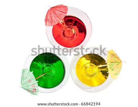 Three multicolored cocktails in martini glasses with umbrellas top view