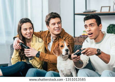 Three multiethnic friends with beagle dog holding joysticks and playing video games