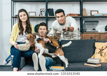 Three multiethnic smiling friends with dog and popcorn sitting on sofa and watching tv