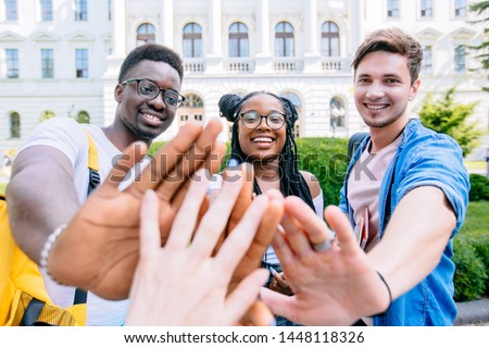 Three multiethnic students greeting you, holding open palms at you, outdoor over university building on background. Diverse Group People High Five Concept.