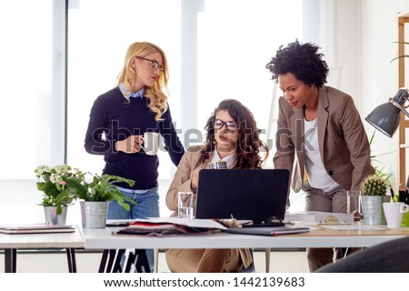 Three multiethnic woman working at the office and drink coffee from mug in front of laptop