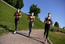 Three multiethnic women runners group wear face masks running keep social distance outdoor. Fit healthy diverse ladies wear sportswear jogging in park on nature sport track distancing for safety.