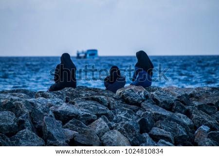 Three muslim girls contemplating the sea from the rocks in Maafushi, Maldives