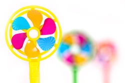 Three muticolored fans in varying levels of focus over a white background