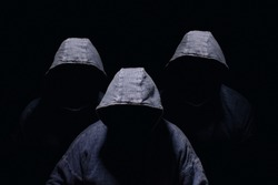 Three mysterious men silhouette with darkened face, no visible face, in blue hoodies on dark background