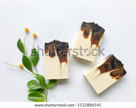 Three natural oil soap with green leaves and yellow mini fruit on white background, cold process, drop and hanger swirl technique, handmade product, black, brown, gray and orange color by herb.