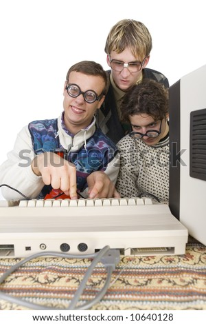 Three nerdy guys sitting in front of old-fashioned computer. One of them is pushing the button on keyboard and looking at camera. front view, white background
