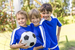 three nice Young boys with soccer ball on a sport uniform